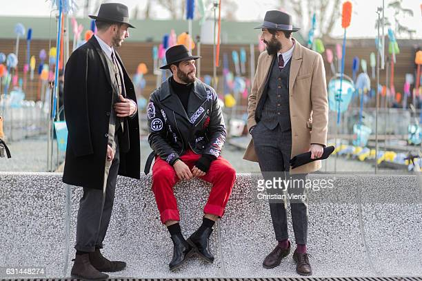 Guests wearing wool coat hat sunglasses red pants suit boots leather shoes on January 10 2017 in Florence Italy