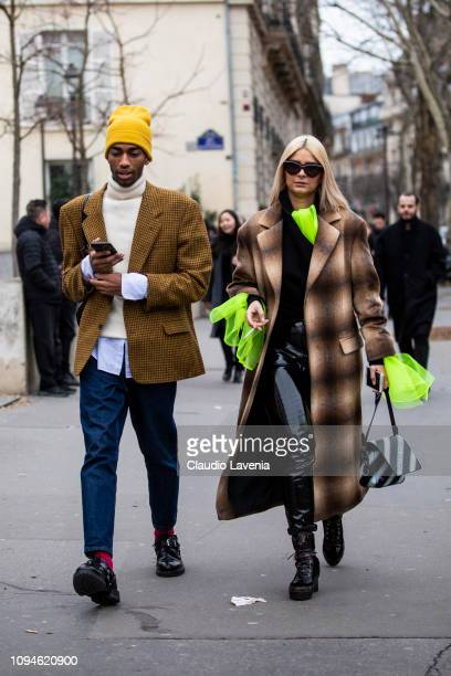 Guests wearing yellow knit cap white turtleneck sweater denim and wool jacket and Off White bag Louis Vuitton boots and wool trench coat are seen in...