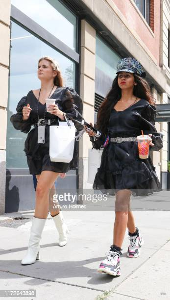 Guests wears black dress black belt with silver buckle and white mid-calf boots; wears stone studded military hat, black dress, studded belt, laced...