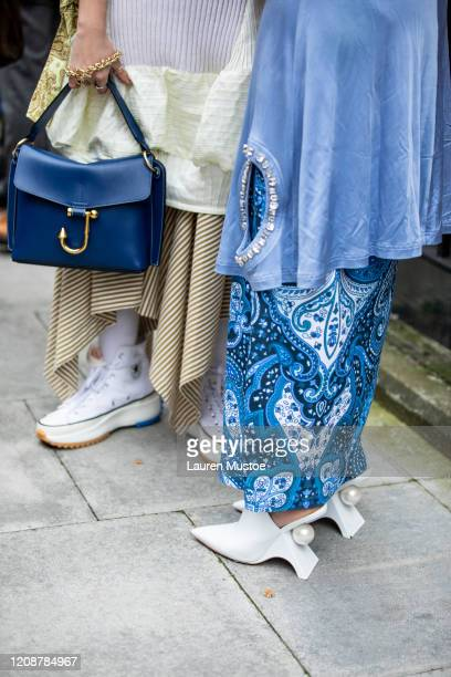 Guests wears JW Anderson bag and pearl heals outside show during London Fashion Week February 2020 on February 17, 2020 in London, England.