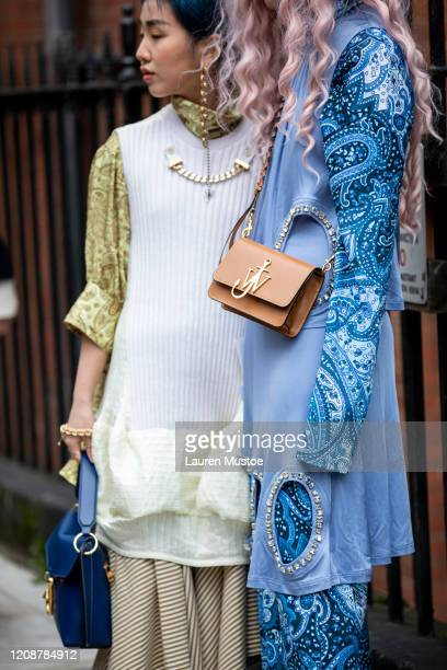 Guests wears JW Anderson jewellery and bag outside show during London Fashion Week February 2020 on February 17, 2020 in London, England.