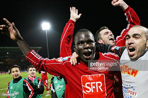 Montceau-les-Mines' Bebe Kambou celebrates with teammate after beating Lens in the French Cup quarter final football match Montceau-les-Mines vs...