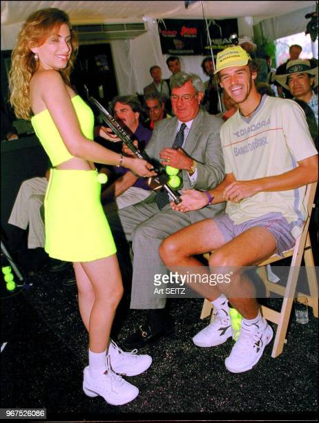 Guga Kuerten is offered a new head racquet by a latino model durng the head racquet press luncheon march 21 200l on Key Biscayne florida during the...