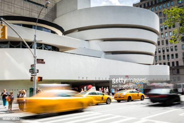 guggenheim in new york with taxis in motion - solomon r. guggenheim museum stock photos and pictures