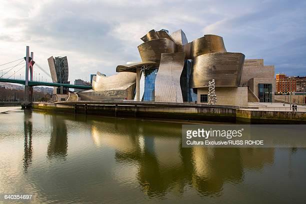 Guggenheim Museum and La Salve bridge reflected in Nervion River, Bilbao, Spain