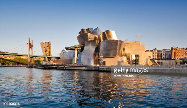 Guggenheim Museum Bilbao, Bilbao, Spain. Architect: Frank Gehry, 1997. General view of riverside elevation with late afternoon sun.