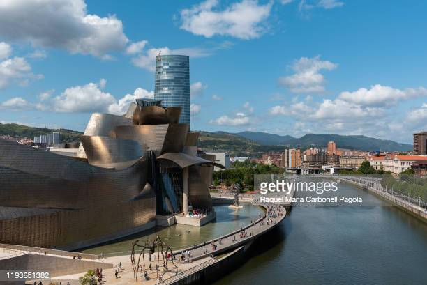 """Guggenheim museum with """"Mamá"""" the spider sculpture in front and Iberdrola tower at back by Nervión river."""