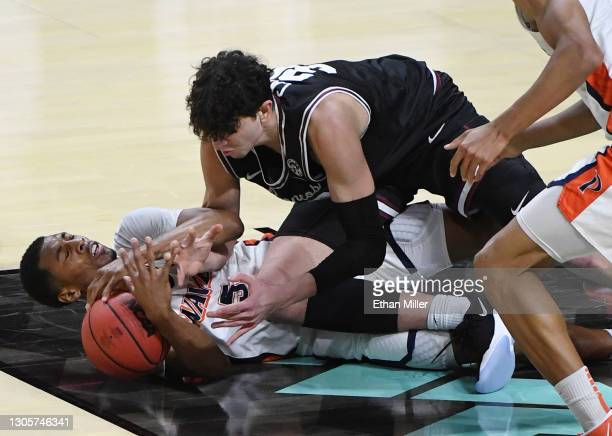 Guglielmo Caruso of the Santa Clara Broncos fouls Jade' Smith of the Pepperdine Waves as they scramble for a loose ball during the West Coast...