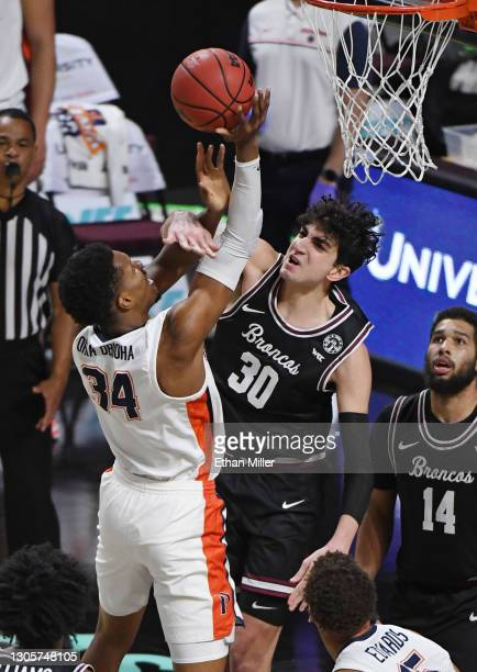 Guglielmo Caruso of the Santa Clara Broncos fouls Victor Ohia Obioha of the Pepperdine Waves during the West Coast Conference basketball tournament...