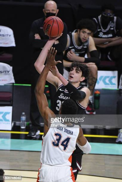 Guglielmo Caruso of the Santa Clara Broncos shoots against Victor Ohia Obioha of the Pepperdine Waves during the West Coast Conference basketball...