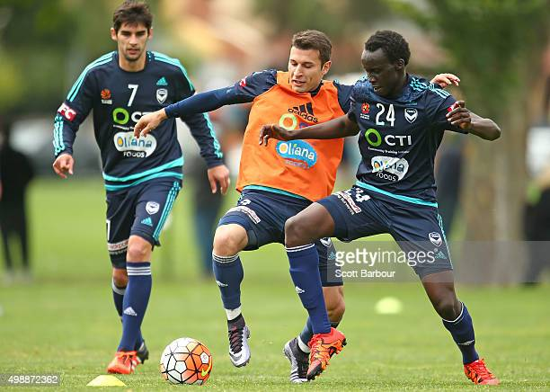 Gui Finkler Kosta Barbarouses and Thomas Deng of the Victory compete for the ball during a Melbourne Victory ALeague training session at AAMI Park on...