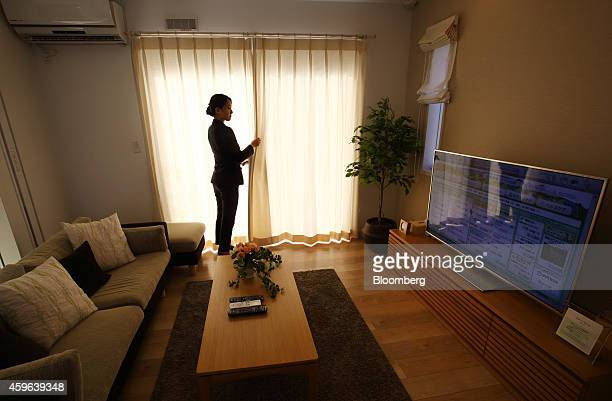 A guide adjusts a window curtain in the dining room of a house built by PanaHome Corp at the Fujisawa Sustainable Smart Town developed by a...