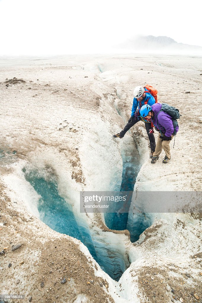 https://www.istockphoto.com/photo/guide-and-senior-woman-peer-into-glacier-moulin-gm599768034-102987387
