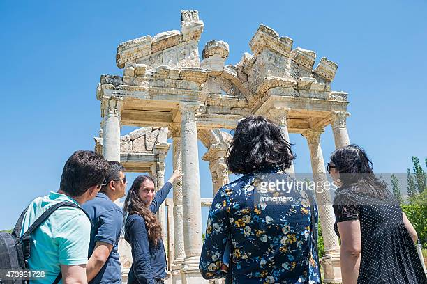 Guide and tourists in front of the Tetrapylon in Aphrodisias,