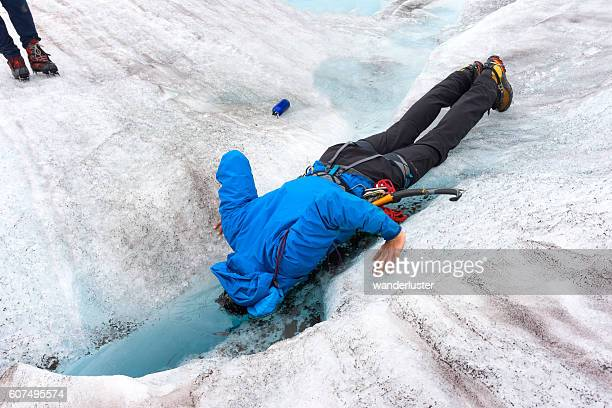 Guide dunks head into freezing glacier pool