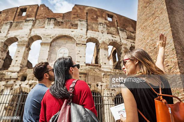 guide explaining to tourists the coliseum of rome - toerisme stockfoto's en -beelden