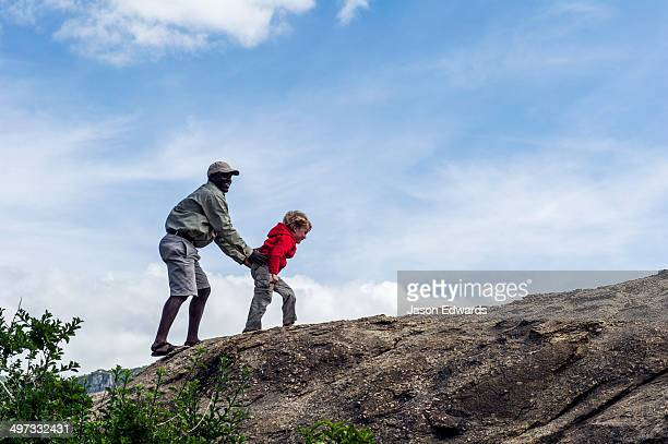 A guide helps a young boy on safari climb a granite outcrop known as a kopje on the savannah.