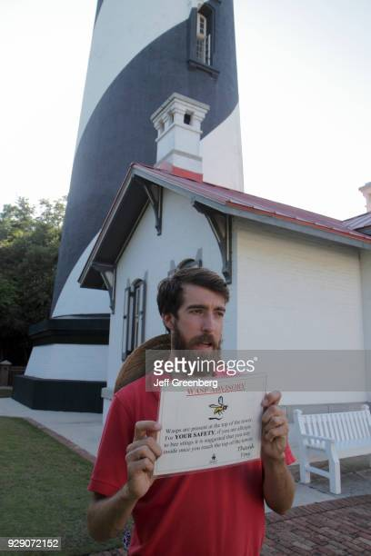 A guide holding a wasp advisory sign at the St Augustine Lighthouse and Museum