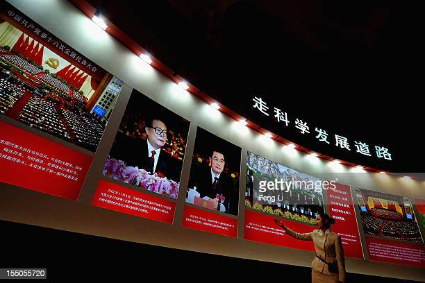 Guide introduces the portraits of China's President Hu Jintao and former President Jiang Zeming as Chinese people visiting an exhibition entitled...