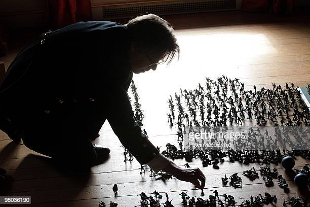Guide known as an 'explainer' re-arranges some of the 10,000 toy soldiers on the floor of The Gallery of War and Play at the Enchanted Palace...