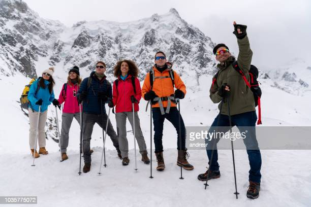 guide leading a group of people trekking in the alps - fare da guida foto e immagini stock