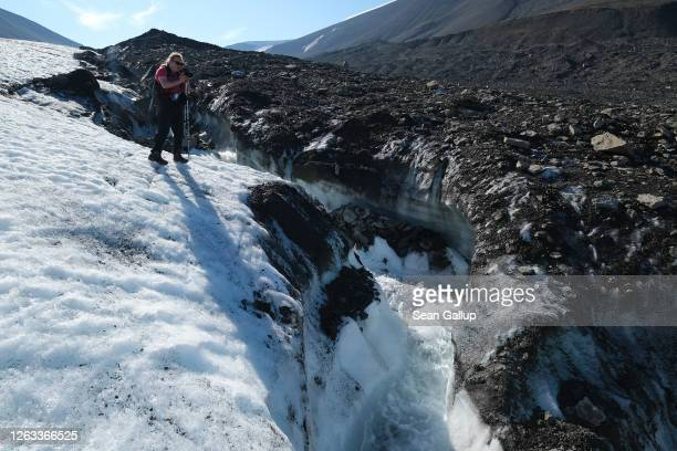 A guide photographs a winding channel carved by water down the surface of the melting Longyearbreen glacier during a summer heat wave on Svalbard...