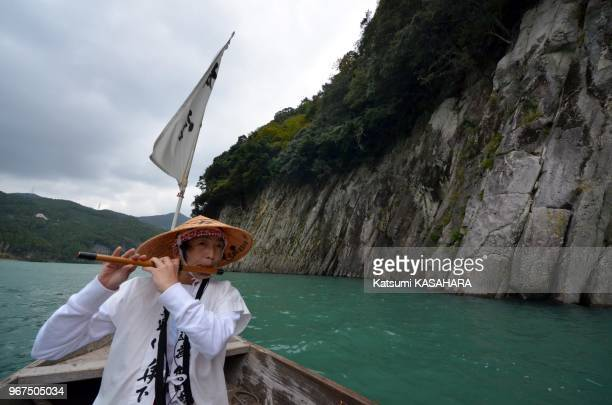 A guide plays a bamboo flute in a tour boat on October 17 2012 on Kumano river in Kumano Japan This Kumano Sanzan area which have been greeting...