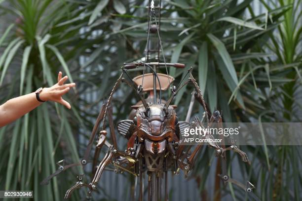 A guide presents a mechanical ant made of wood and steel walks at the Machine Gallery of 'Les Machines de L'Ile' in Nantes western France on June 20...