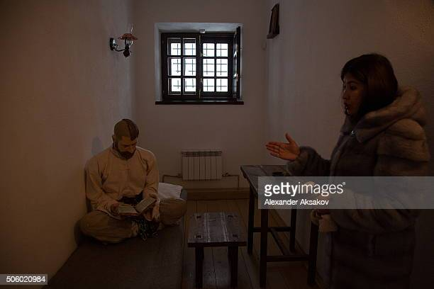 A guide shows a single cell in the museum of the Prison Castle in Tobolsk Russia on January 21 2016 A dummy of a prisoner reads the Bible One half of...