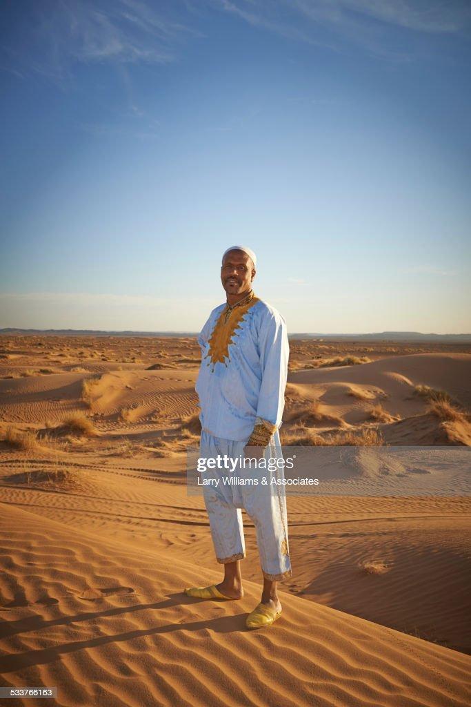 Guide smiling on sand dunes in desert landscape : Foto stock