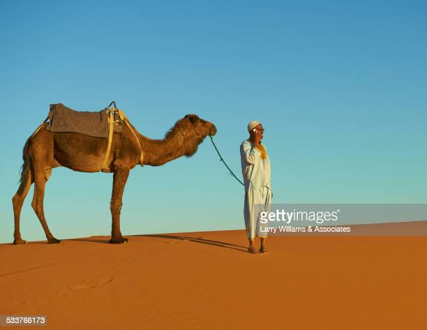 Guide talking on cell phone with camel on sand dune