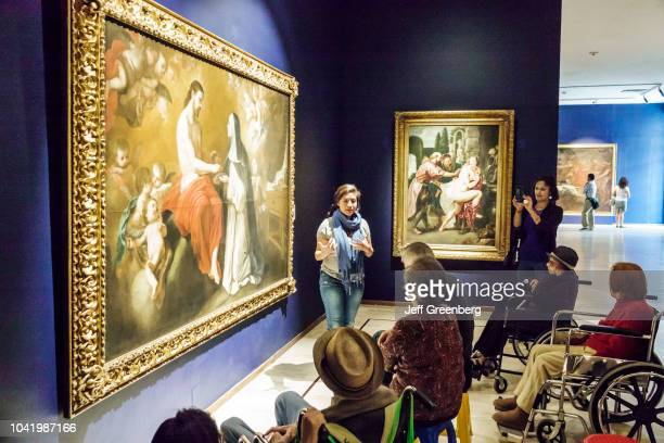 A guide talking to people in front of a European painting in the San Carlos National Museum