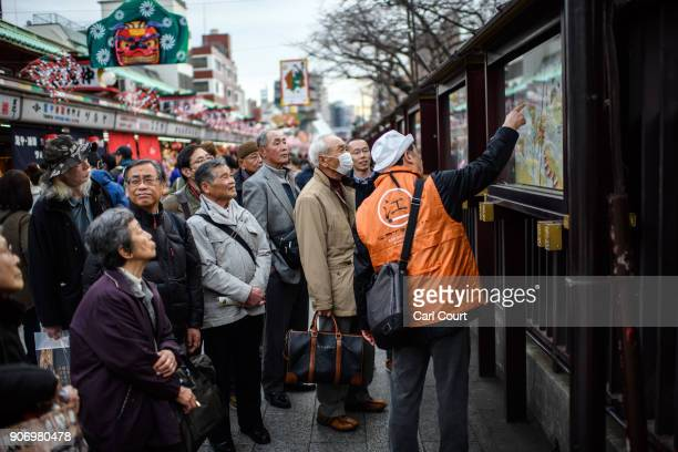 A guide talks to a tour group as they visit Sensoji buddhist temple on January 19 2018 in Tokyo Japan Sensoji is Tokyo's oldest temple dating back to...