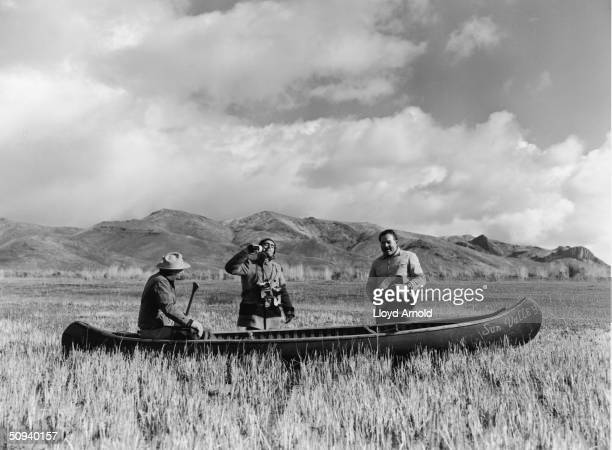 Guide Taylor Williams photographer Robert Capa and author Ernest Hemingway pose with a canoe while on a duck hunt in Sun Valley Idaho November 13...