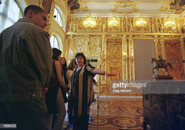 A guide tells tourists about the amber room part of which has been restored by Russian craftsmen July10 2000 in St Catherine''s Palace in Tsarskoye...