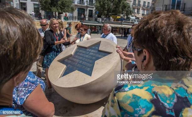 A guide tells tourists about the 'Lisbon Massacre' also known as the 'Lisbon Pogrom' or the '1506 Easter Slaughter' an incident in which a crowd of...