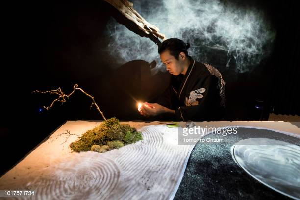 A guide wearing a kimono lights incense in the waiting room of the Tree by Naked Yoyogi Park restaurant produced by Naked Inc on August 16 2018 in...