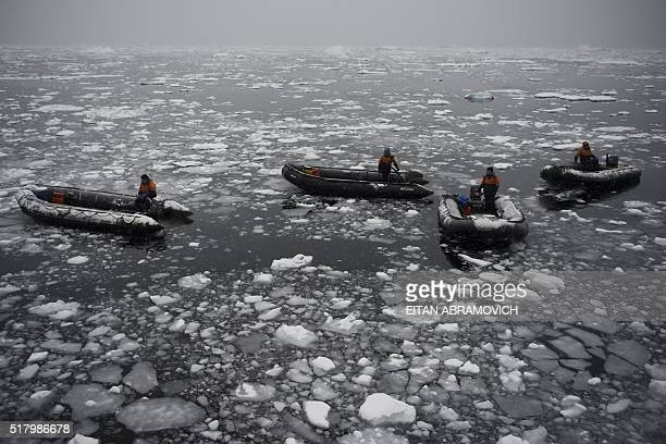 Guides wait for tourists to board thier rubber dinghies to cruise the western Antarctic peninsula on March 05, 2016. The Antarctic tourism industry...