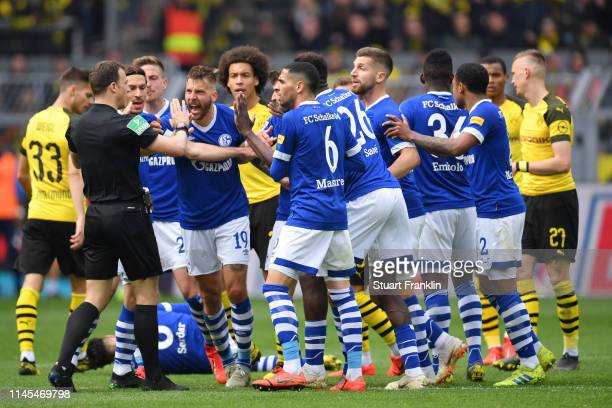 Guido Burgstaller of FC Schalke 04 and his team mates protests to referee Felix Zwayer during the Bundesliga match between Borussia Dortmund and FC...