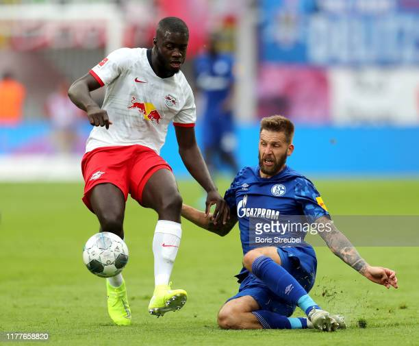 Guido Burgstaller of FC Schalke 04 battles for possession with Dayot Upamecano of RB Leipzig during the Bundesliga match between RB Leipzig and FC...