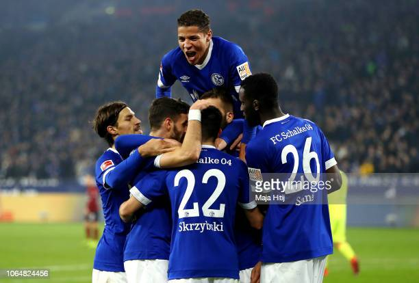 Guido Burgstaller of FC Schalke 04 celebrates with teammates after scoring his team's third goal during the Bundesliga match between FC Schalke 04...