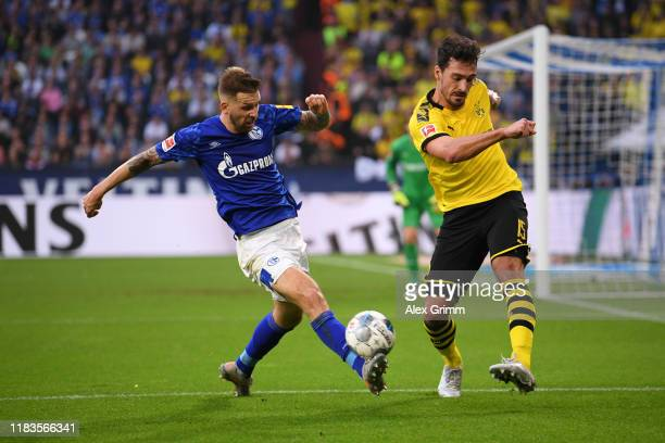 Guido Burgstaller of FC Schalke 04 is challenged by Mats Hummels of Borussia Dortmund during the Bundesliga match between FC Schalke 04 and Borussia...