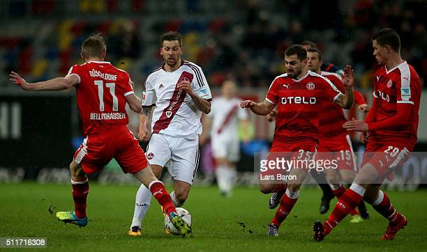 Guido Burgstaller of Nuernberg is challenged by Axel Bellinghausen of Duesseldorf Charalampos Mavrias of Duesseldorf and Alexander Madlung of...