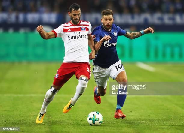 Guido Burgstaller of Schalke 04 is challenged by Mergim Mavraj of Hamburger SV during the Bundesliga match between FC Schalke 04 and Hamburger SV at...