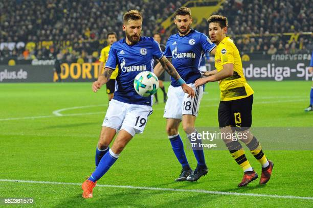 Guido Burgstaller of Schalke and Daniel Caligiuri of Schalke and Raphael Guerreiro of Dortmund battle for the ball during the Bundesliga match...