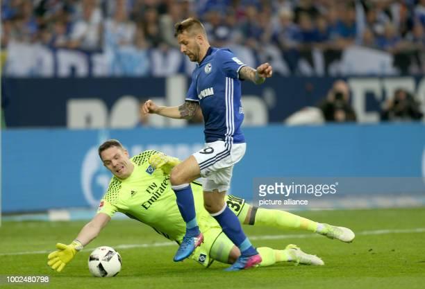 Guido Burgstaller of Schalke and Hamburg's goalkeeper Christian Mathenia vie for the ball during the German Bundesliga soccer match between FC...
