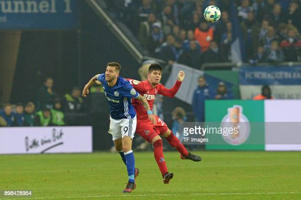Guido Burgstaller of Schalke and Jorge Mere of Koeln battle for the ball during the Bundesliga match between FC Schalke 04 and 1 FC Koeln at...