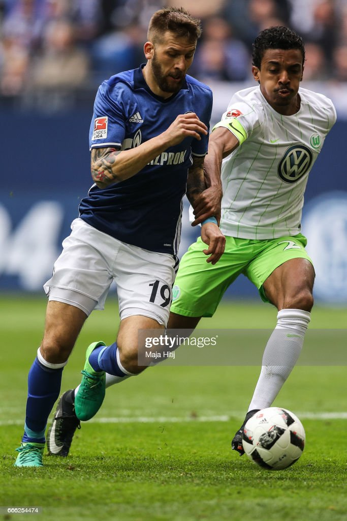 Guido Burgstaller of Schalke (R) and Luiz Gustavo of Wolfsburg battle for the ball during the Bundesliga match between FC Schalke 04 and VfL Wolfsburg at Veltins-Arena on April 8, 2017 in Gelsenkirchen, Germany.