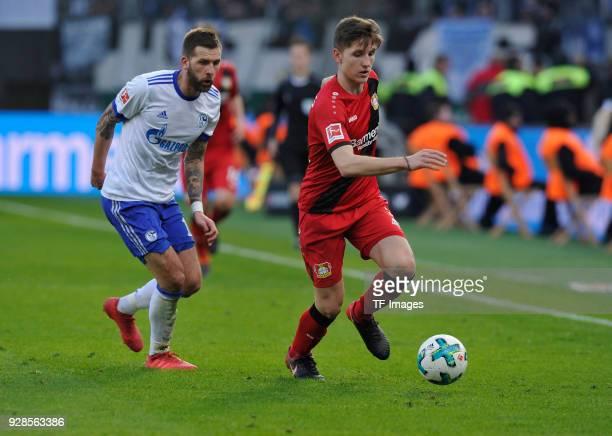 Guido Burgstaller of Schalke and Panagiotis Retsos of Leverkusen battle for the ball during the Bundesliga match between Bayer 04 Leverkusen and FC...