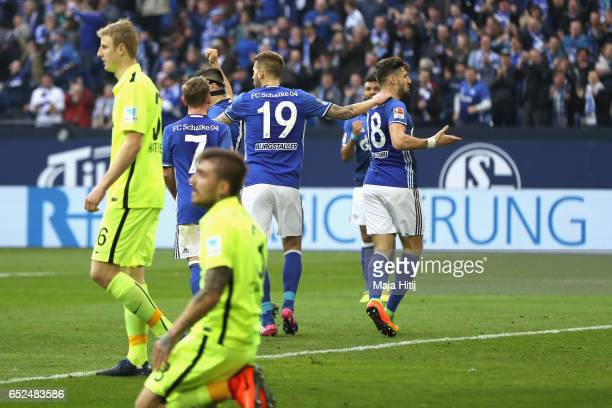 Guido Burgstaller of Schalke celebrates the second team goal with his team mate Daniel Caligiuri whilst Konstatntinos Stafylidis of Augsburg looks...